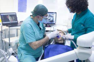 Dentist examining molar area using UV ray